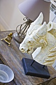 A carved white horse's head on a wooden table