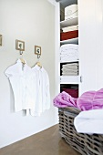 White blouses on hangers in the corner of a bathroom