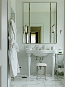 A built in mirrored cupboard in a white bathroom with a marble floor