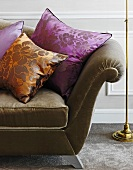 Cushions made of a shiny orange and purple material on a sofa