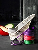 Coils of colourful hose next to a wicker chair and floor lights