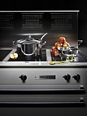 A pot and kitchen utensils on a cooker with a chrome extractor hood