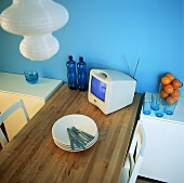 A dining table in front of a blue wall with crockery, cutlery and a television