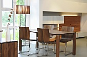 A dining room with a walnut dining table and chairs in designer style