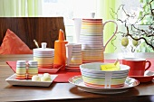 Colourful, striped breakfast crockery and coffee pot and Easter decoration