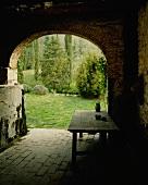 A view through an old archway onto an idyllic garden