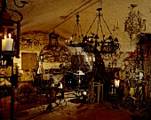 A collection of old chandeliers and candle holders in a cellar