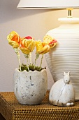A decorated Easter nest with yellow fabric flowers and a ceramic rabbit