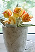 A grey stone pot decorated with fabric flowers