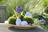An Easter nest on a garden table with flowers and moss