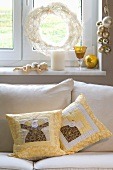 Sofa cushions with an angel motif under a festively decorated window