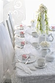 A wedding reception table decked in white with dessert on the plates