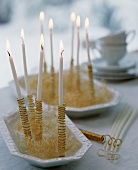 Candles wrapped in gold thread with tinsel
