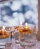 Floating candles in glasses decorated with beads