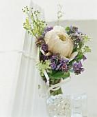 Blumenstrauss mit violetten Blüten und einer weissen Blume