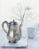 Snowdrops in a teapot decorated with wire