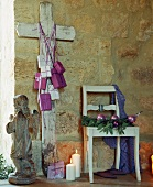 A wooden cross leaning against a wall of a rustic house decorated for Christmas
