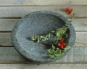 A sprig of rosehips in a stone bowl