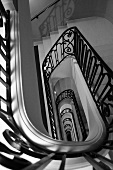A stairway of a manor house with a black banister