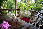 A chess board set out on the terrace in tropical surroundings