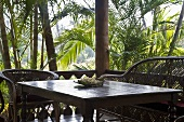 Wicker furniture in the corner of a terrace in tropical surroundings