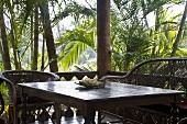 Terrasseneckplatz mit Korbmöbel auf der Veranda in tropischer Umgebung