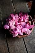 Eine Schale mit violetten Lotusblüten auf dem Holzboden