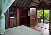 A wood panelled bedroom with view of a terrace and palm trees