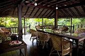 Überdachter Terrassenplatz mit Korbmöbel und Kugelleuchten in tropischer Umgebung