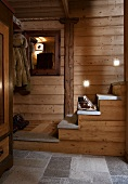 A wood panelled hallway with stairs in a hut