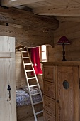 A bunk bed in a wood panelled attic room