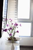 A delicate bunch of purple flowers on a white shelf