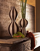 Still life - black and white striped vases on concrete furniture with a back wall