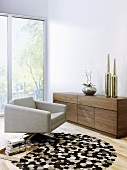 A designer living room - swivel armchair on a round rug and a wooden sideboard in front of a floor-to-ceiling window