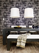 White lampshades hanging above a table and an upholstered bench against a black and white papered wall