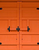 Detail of an orange-painted entrance door with a wrought iron bolt