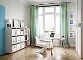 Büro mit Schreibtisch, Freischwinger Stuhl und Büroegal