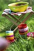 Bunte Schälchen im Gras und grössere Schalen auf Klappstuhl
