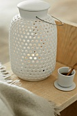 A white ceramic lantern with a cup of tea next to it