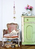 Baroque style chair next to a country style chest of drawers