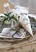 Blumenvase und Postkarten auf Tablett aus geflochtener Weide