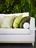 Sofa upholstered in white with pillows