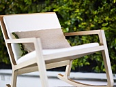 Swing frame chair out of wood with pillow
