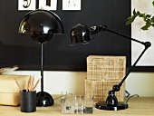 Black table lamps and writing implements on a light colored shelf