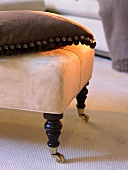Antique ottoman with castors and a pillow
