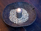 Lighted candle and decorative stones in a rustic wooden bowl