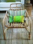 Rattan chair with striped pillow on rustic wood flooring