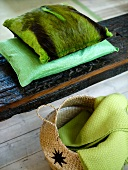 Green pillows with a pelt cover on wooden planks and basket with a coverlet