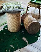 Wooden stools with pillows and a leaf shaped mat