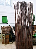 Screen made of willow branches and willow basket on a stool